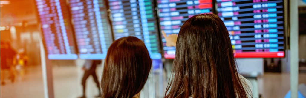 Two girls looking at the information board to check their flight status